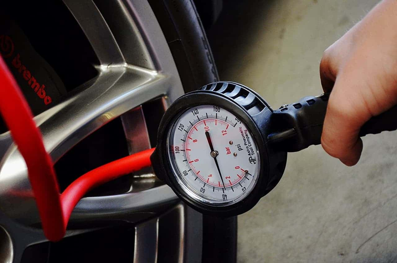 Using a tire inflator to check tire pressure Image