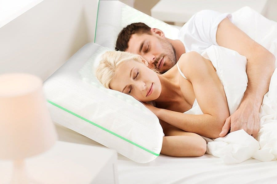 Couple sleeping together while resting their heads on cooling pillows