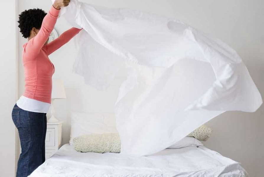 Picture of a woman putting sheets on her bed